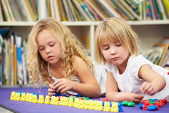 Two Elementary Pupils Counting Together In Classroom. Lying Down Concentrating Stock Photos