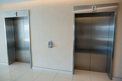 Two elevator doors in lobby of office building. Two modern elevator doors in lobby of office building stock image