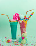 Two elicious homemade extreme milkshake, with a blackberry candy over a milk foam and a rainbow candy on top with a Stock Photography