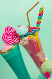 Two elicious homemade extreme milkshake, with a blackberry candy over a milk foam and a rainbow candy on top with a Stock Image