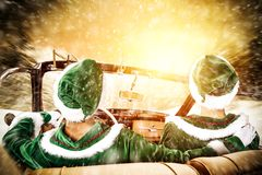 Two Elves in a car driving to deliver some christmas presents on a sunny winter day. Christmas decor on gold red background.