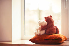 Two embracing living teddy bear toys sitting on window-sill. Two embracing loving teddy bear toys sitting on window-sill. With retro filter Royalty Free Stock Photography