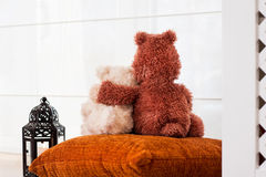 Two embracing loving teddy bears sitting on window-sill. Love an Stock Photography