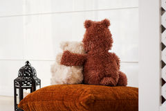 Two embracing teddy bears. Looking through the window sitting on window-sill Royalty Free Stock Image