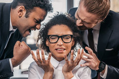 Two emotional businessmen in formalwear screaming on businesswoman in office. Multicultural business team Stock Images