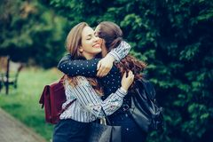 Two emotional happy woman friends hugging each other outdoors stock photography