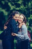 Two emotional happy woman friends hugging each other in the park royalty free stock images