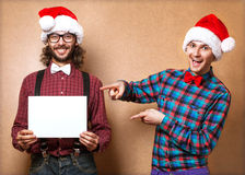 Two emotional Santa Claus. Photo of two men in clothes of Santa Claus hand in pointing gesture Royalty Free Stock Images