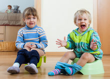 Two emotional siblings on chamber pots. Two emotional siblings sitting on chamber pots in home interior stock photos