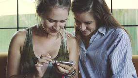 Two emotional woman friends use smartphone in cafe. Caucasian models with long hair stock footage