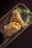 Two empanadas and a glass of wine in a chic retreat. Royalty Free Stock Photos