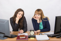 Two employee in the office looking at the clock and waiting for the end of the working time Royalty Free Stock Image