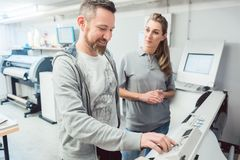 Two employees in advertising agency operating large format printer. On touchscreen stock photo