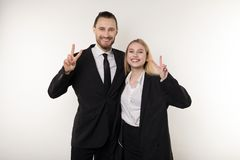 Two employees laugh happily at the end of the working week, showing viktory sign and looking at the camera stock photos