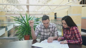 Two employees sit at desk and discuss schemes and graphics inside. stock footage