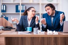 The two employees suffering at workplace. Two employees suffering at workplace royalty free stock image