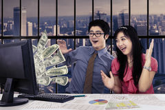 Two employess earning money online Stock Photography