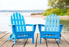 Blue adirondak chairs on wooden pier by lake in summer stock photos