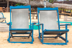 Two empty blue deckchairs at beach. Stock Photos