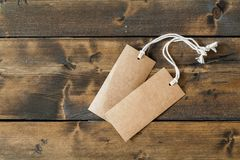 Two empty cardboard tags ready for text. Or other concept, laying on a wooden floor Stock Photos
