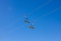 Two empty chair lift seats against blue sky Royalty Free Stock Images