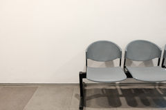 Two empty chairs by concrete wall background with copy space Royalty Free Stock Images
