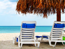 Two empty chairs by the sea. Two lounge chairs waiting for someone under a palapas at the beach of a tropical resort Stock Photography