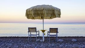 Two empty chairs stand on beach under open umbrella. Overlooking the marine sunrise Stock Photo