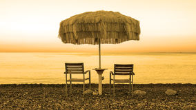 Two empty chairs stand on beach under open umbrella. Overlooking the marine sunrise Royalty Free Stock Photo