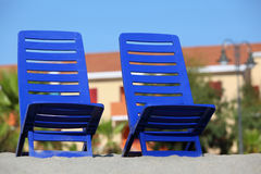 Two empty chairs stand on sand under sun Royalty Free Stock Photo