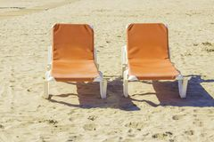 Two empty chaise lounges on the sand. Of the beach royalty free stock photos