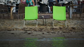 Two empty chaise-lounges with table on the beach stock video footage