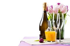 Two empty champagne flutes and a bottle of sparkling wine. With tulips on background royalty free stock image