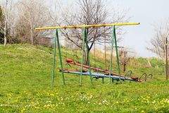 Two empty children swings and seesaw at playground activities in public park / Natural environment, grass, spring flowers. Royalty Free Stock Photography