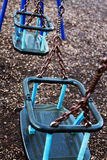 Two empty childrens swings in a play park. Two childrens swings in a play park royalty free stock image
