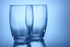 Two empty clean glasses for water or alcohol blue color. Background Stock Image