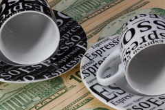 Two empty coffee cups  and US dollar banknotes Stock Photo