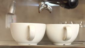 Two empty Cup pour steaming hot before cooking the coffee. Coffee house. Close-up of two white cups of coffee are in the coffee machine. Preparation of espresso stock footage