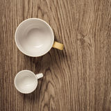 Two empty cups on wooden floor Stock Photo