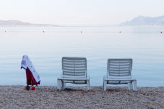 Two empty deck chair and a bag on wheels Stock Photo