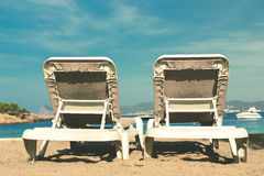 Two empty deckchairs on a sandy beach facing the ocean, blue skies and a small speed boat Royalty Free Stock Images
