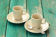 Two empty ebony espresso cups with silver spoon on turquoise sha Royalty Free Stock Images