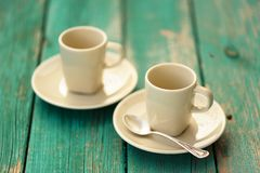 Two empty ebony espresso cups with silver spoon on turquoise shabby Royalty Free Stock Photo
