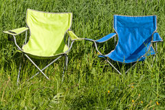 Two empty folding chair on the green grass Stock Photos