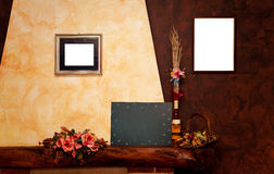 Two empty frames, and blackboard  on yellow and brown wall. Two empty frames, a blackboard, a bottle,  on yellow and brown wall Stock Images