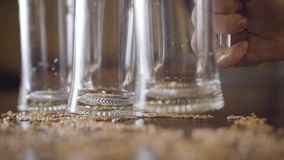 Two empty glass of beer standing on the table in the bar close-up. Male hand putting third glass on the table. Barley stock video footage