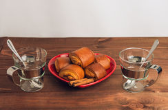 Two empty glass cups with metal handles and cinnamon rolls on a Royalty Free Stock Image