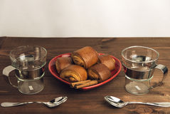Two empty glass cups with metal handles and cinnamon rolls on a Royalty Free Stock Photo