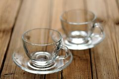 Two empty glass teacups on wooden background selective focus Stock Photos