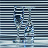 Two empty glasses with bands of refraction blinds. Two empty glasses with refraction bands of blinds in the background and blue backlight Royalty Free Stock Photo